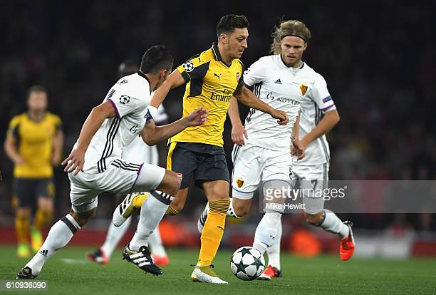 Mesut Ozil of Arsenal runs with the ball under pressure from Marek Suchy and Birkir Bjarnason of Basel during the UEFA Champions League group A match...