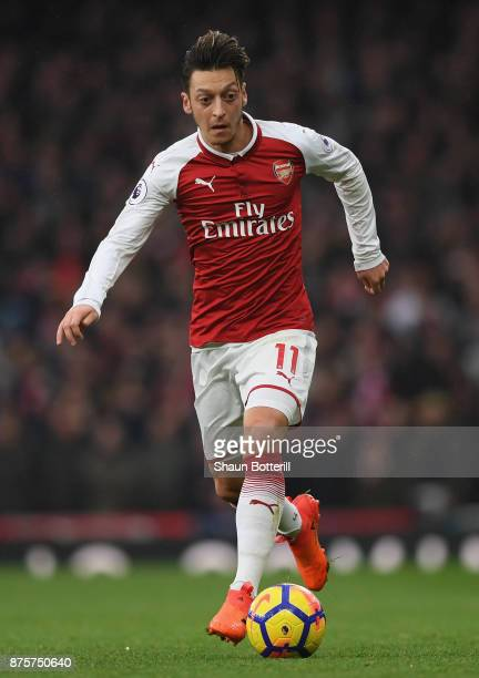 Mesut Ozil of Arsenal runs with then ball during the Premier League match between Arsenal and Tottenham Hotspur at Emirates Stadium on November 18...