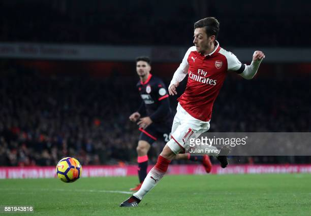 Mesut Ozil of Arsenal scores his sides fourth goal during the Premier League match between Arsenal and Huddersfield Town at Emirates Stadium on...