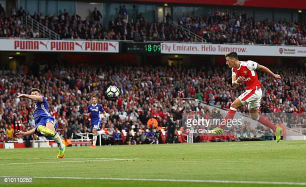 Mesut Ozil of Arsenal scores his sides third goal during the Premier League match between Arsenal and Chelsea at the Emirates Stadium on September 24...