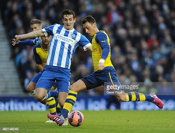 Mesut Ozil of Arsenal scores their second goal under pressure from Lewis Dunk of Brighton during the FA Cup Fourth Round match between Brighton Hove...