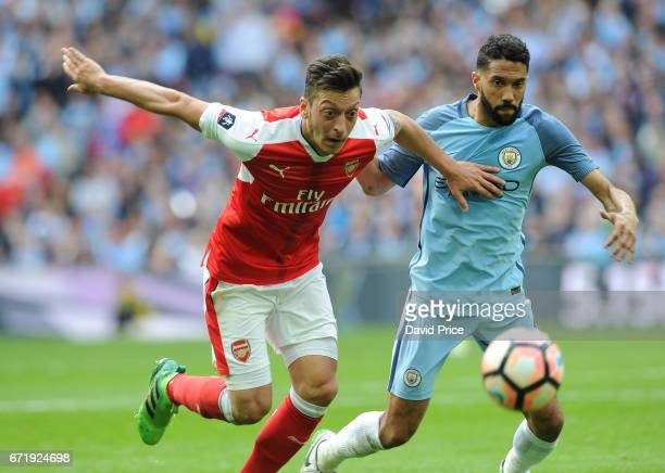 Mesut Ozil of Arsenal takes on Gael Clichy of Manchester City during the match between Arsenal and Manchester City at Wembley Stadium on April 23...