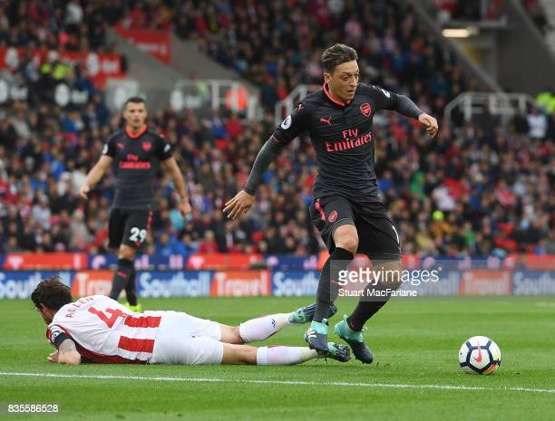 Mesut Ozil of Arsenal takes on Joe Allen of Stoke during the Premier League match between Stoke City and Arsenal at Bet365 Stadium on August 19 2017...