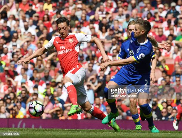 Mesut Ozil of Arsenal takes on Morgan Schneiderlin of Everton during the Premier League match between Arsenal and Everton at Emirates Stadium on May...