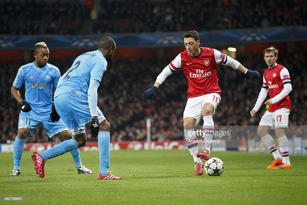 Mesut Ozil of Arsenal (R) vies for the ball during the UEFA Champions League group F football match between Arsenal and Olympique de Marseille at the Emirates Stadium on November 26, 2013 in London, England.