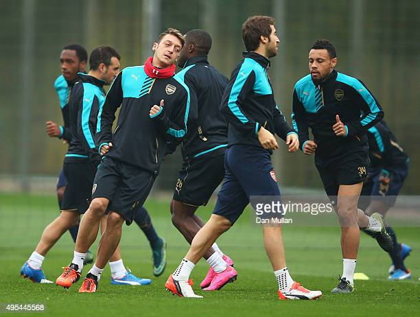 Mesut Ozil of Arsenal warms up with team mates during an Arsenal training session on the eve of the UEFA Champions League Group F match against...