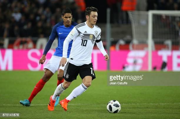 Mesut Ozil of Germany Raphael Varane of France during the international friendly match between Germany and France at RheinEnergieStadion on November...
