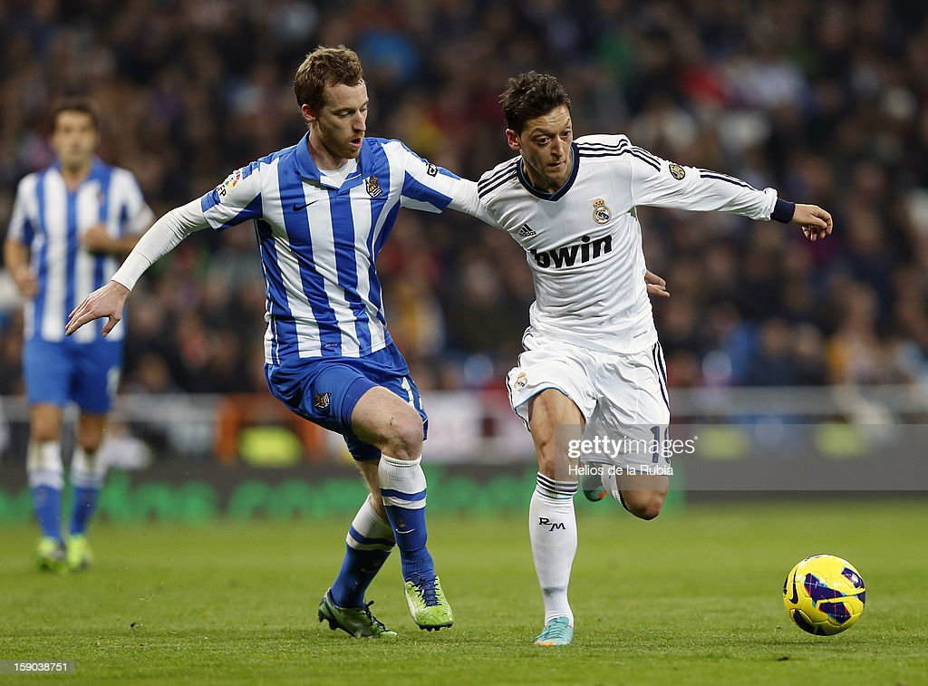 Mesut Ozil (R) of Real Madrid and David Zurutuza of Real Sociedad compete for the ball during the La Liga match between Real Madrid and Real Sociedad at Estadio Santiago Bernabeu on January 6, 2013 in Madrid, Spain.