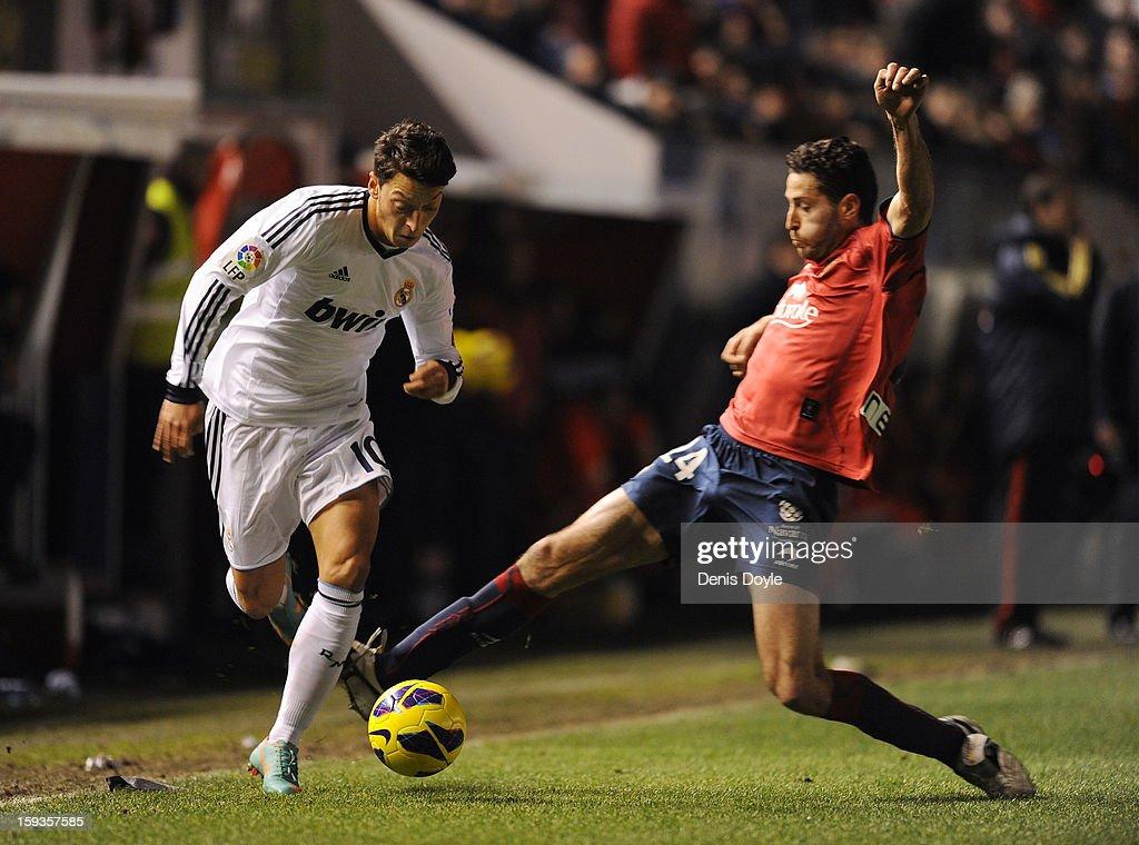Mesut Ozil (L) of Real Madrid battles for the ball against Alejandro Arribas of Osasuna during the La Liga match between Osasuna and Real Madrid at estadio Reino de Navarra on January 12, 2013 in Pamplona, Spain.