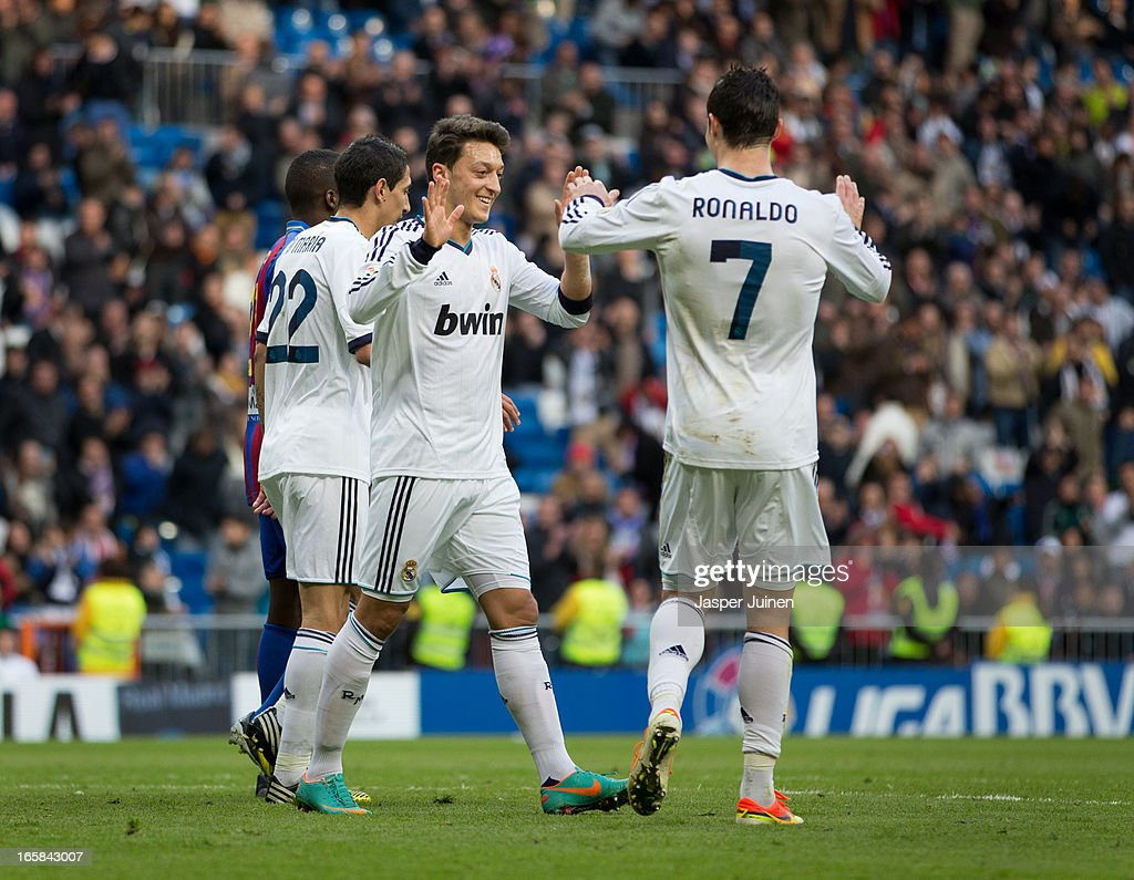 Mesut Ozil (C) of Real Madrid celebrates scoring with his teammate Cristiano Ronaldo (R) during the la Liga match between Real Madrid CF and Levante UD at Estadio Santiago Bernabeu on April 6, 2013 in Madrid, Spain.