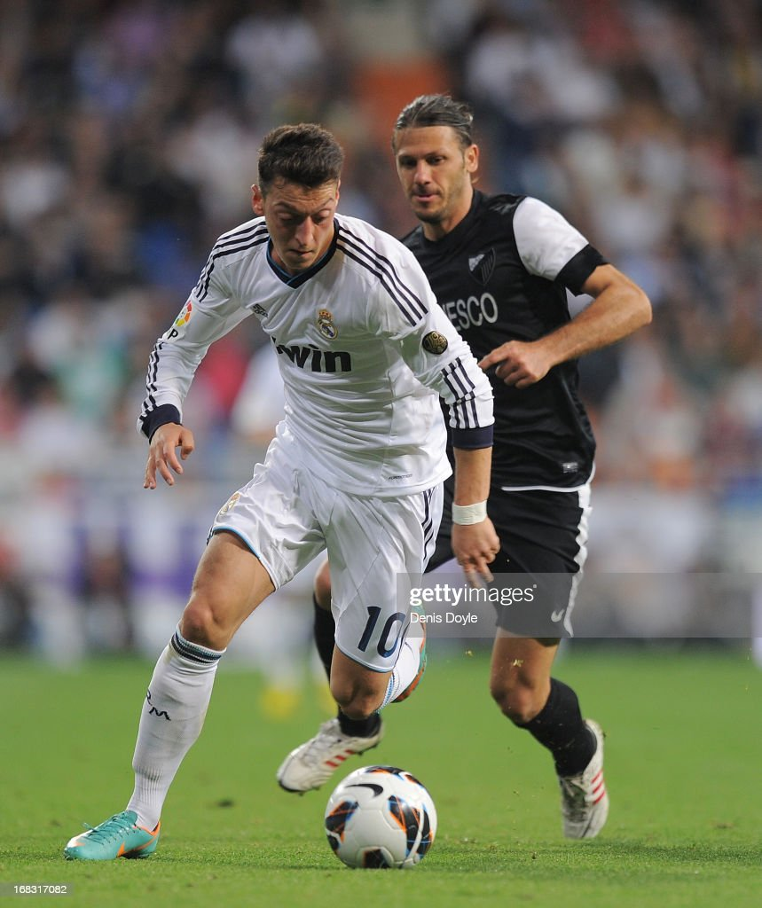 Mesut Ozil (L)of Real Madrid CF beats <a gi-track='captionPersonalityLinkClicked' href=/galleries/search?phrase=Martin+Demichelis&family=editorial&specificpeople=240330 ng-click='$event.stopPropagation()'>Martin Demichelis</a> of Malaga CF during the La Liga match between Real Madrid CF and Malaga CF at estadio Santiago Bernabeu on May 8, 2013 in Madrid, Spain.
