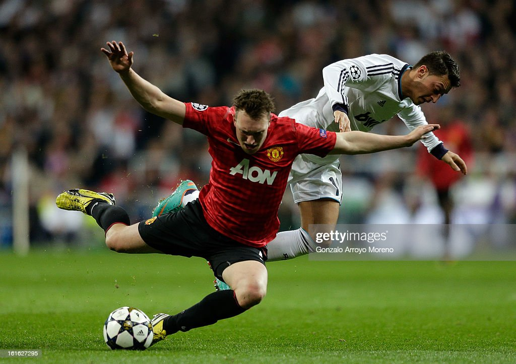 Mesut Ozil of Real Madrid clashes with Phil Jones of Manchester United during the UEFA Champions League Round of 16 first leg match between Real Madrid and Manchester United at Estadio Santiago Bernabeu on February 13, 2013 in Madrid, Spain.