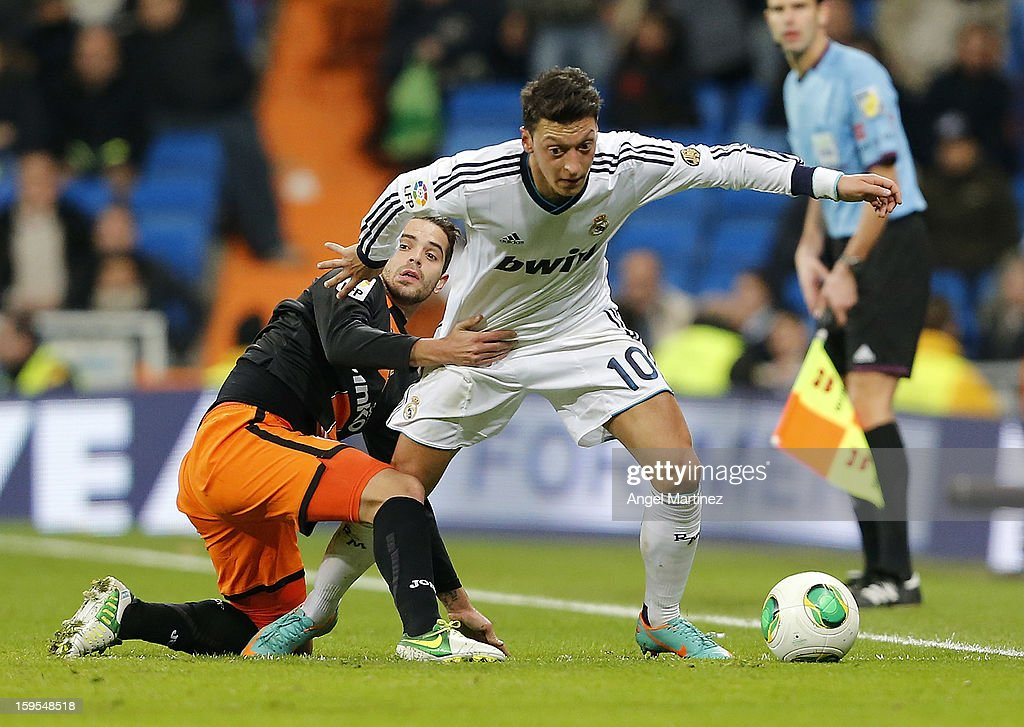 Mesut Ozil of Real Madrid competes for the ball with <a gi-track='captionPersonalityLinkClicked' href=/galleries/search?phrase=Fernando+Gago&family=editorial&specificpeople=674234 ng-click='$event.stopPropagation()'>Fernando Gago</a> of Valencia during the Copa del Rey quarter-final, first leg match between Real Madrid and Valencia at Estadio Santiago Bernabeu on January 15, 2013 in Madrid, Spain.