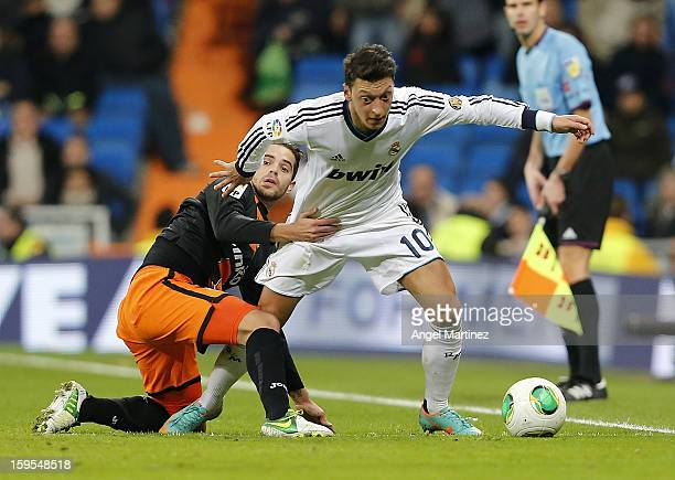Mesut Ozil of Real Madrid competes for the ball with Fernando Gago of Valencia during the Copa del Rey quarterfinal first leg match between Real...