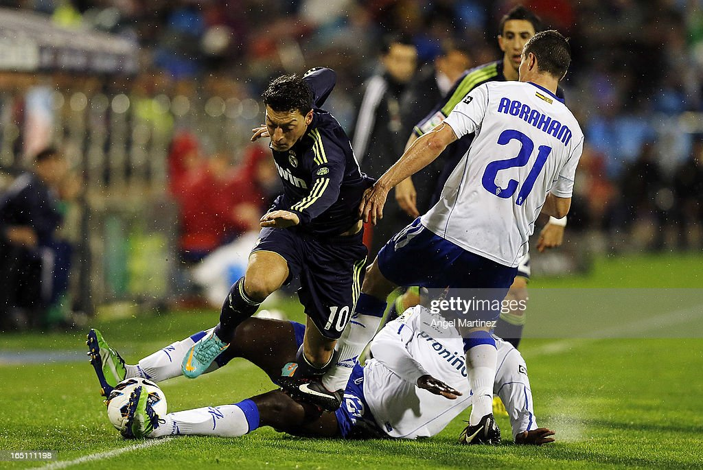 Mesut Ozil of Real Madrid is challenged by Abraham Minero (R) and Ndri Romaric of Real Zaragoza during the La Liga match between Real Zaragoza and Real Madrid at La Romareda on March 30, 2013 in Zaragoza, Spain.