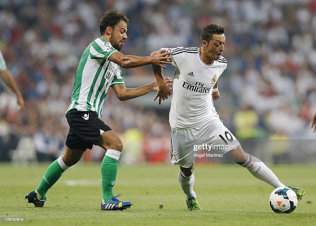 Mesut Ozil of Real Madrid is challenged by Javier Matilla of Betis during the La Liga match between Real Madrid CF and Real Betis at Estadio Santiago Bernabeu on August 18, 2013 in Madrid, Spain.