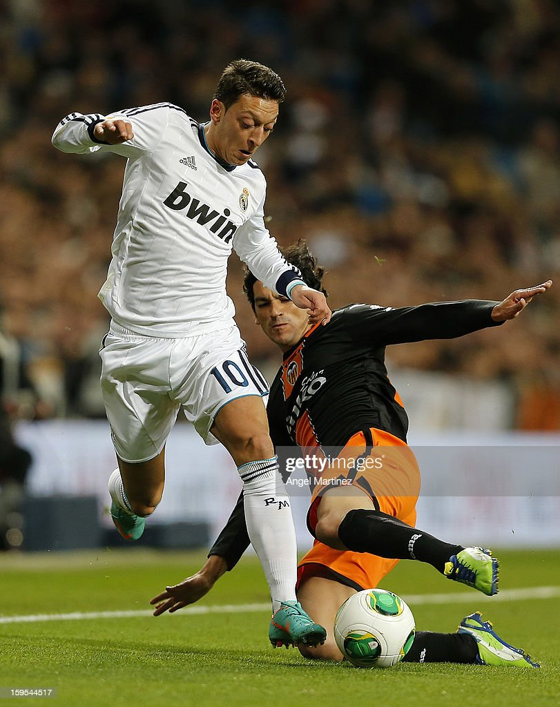 Mesut Ozil of Real Madrid is challenged by <a gi-track='captionPersonalityLinkClicked' href=/galleries/search?phrase=Tino+Costa&family=editorial&specificpeople=7085501 ng-click='$event.stopPropagation()'>Tino Costa</a> of Valencia during the Copa del Rey quarter-final first leg match between Real Madrid and Valencia at Estadio Santiago Bernabeu on January 15, 2013 in Madrid, Spain.