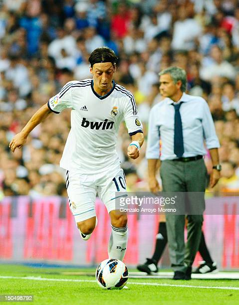 Mesut Ozil of Real Madrid runs with the ball behind him Head coach jose Mourinho during the La Liga match between Real madrid and Valencia at Estadio...
