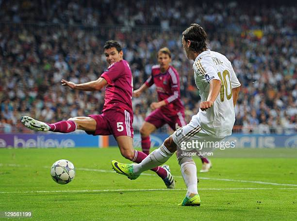 Mesut Ozil of Real Madrid scores his sides third goal past Dejan Lovren of Olympique Lyonnais during the UEFA Champions League group D match between...