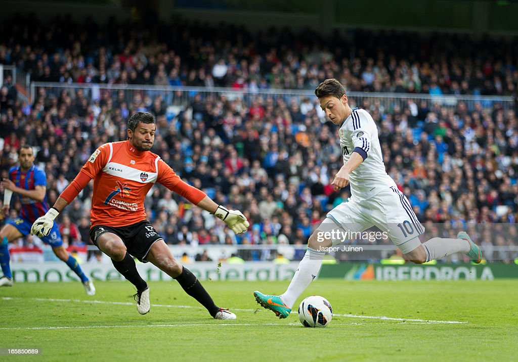 Mesut Ozil (R) of Real Madrid shoots on goal past goalkeeper Gustavo Munua of Levante during the la Liga match between Real Madrid CF and Levante UD at Estadio Santiago Bernabeu on April 6, 2013 in Madrid, Spain.
