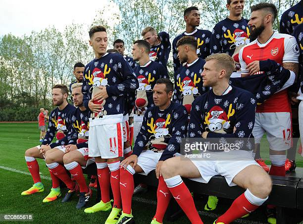 Mesut Ozil Santi Cazorla and Per Mertesacker of Arsenal in their Christmas Jumpers to support Save the Children Christmas Jumper Day at London Colney...
