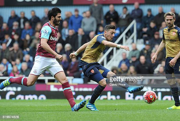 Mesut Ozil scores a goal for Arsenal as James Tomkins of West Ham looks on during the Barclays Premier League match between West Ham United and...