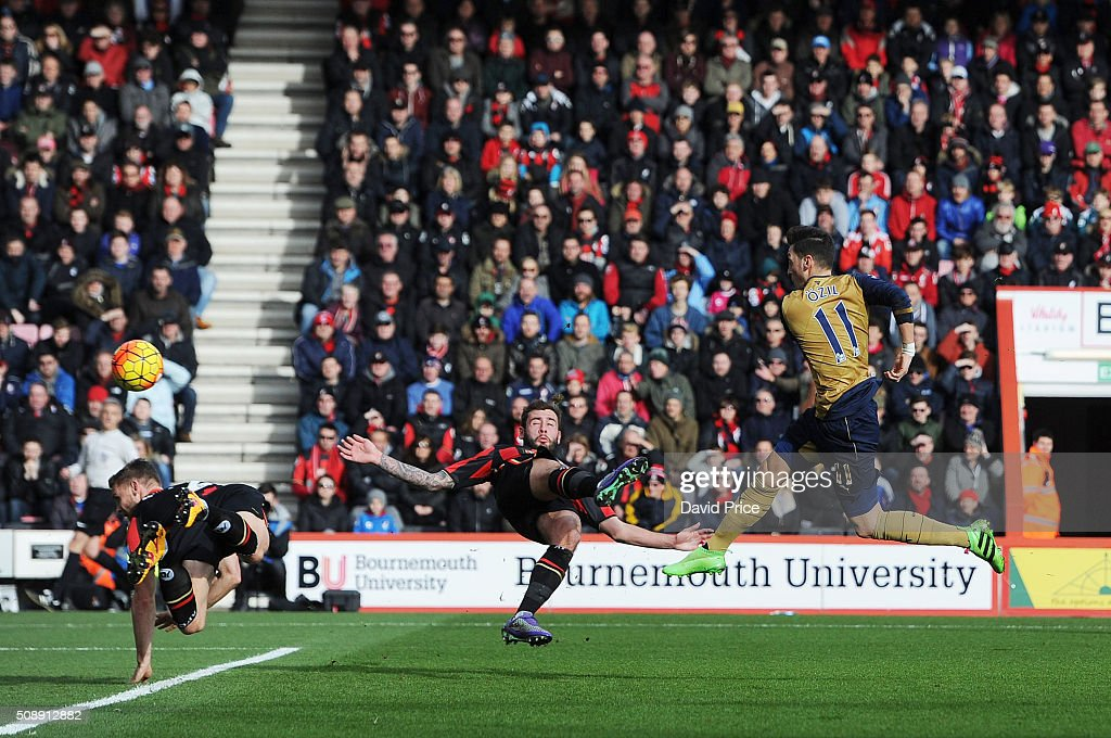 Mesut Ozil scores Arsenal's 1st goal under pressure from Steve Cook of Bournemouth during the Barclays Premier League match between AFC Bournemouth and Arsenal at The Vitality Stadium, Bournemouth 7th February 2016.
