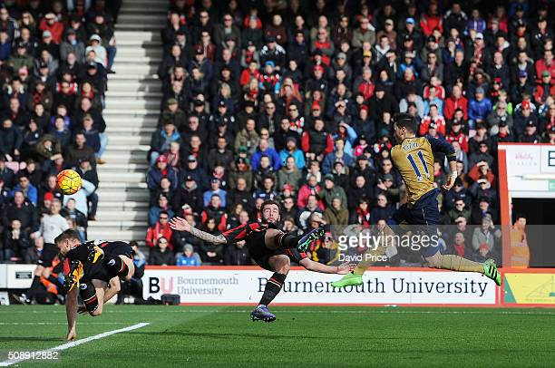 Mesut Ozil scores Arsenal's 1st goal under pressure from Steve Cook of Bournemouth during the Barclays Premier League match between AFC Bournemouth...