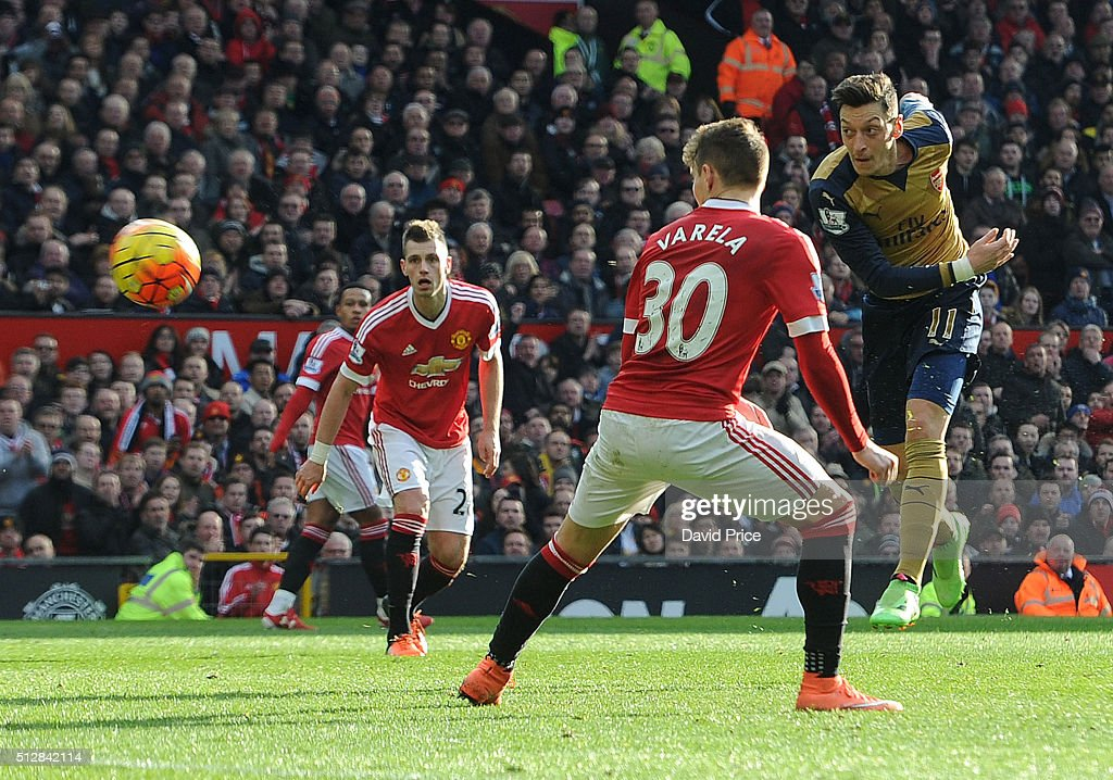 Mesut Ozil scores Arsenal's 2nd goal under pressure from <a gi-track='captionPersonalityLinkClicked' href=/galleries/search?phrase=Guillermo+Varela&family=editorial&specificpeople=10113482 ng-click='$event.stopPropagation()'>Guillermo Varela</a> of Man Utd during the Barclays Premier League match between Manchester United and Arsenal at Old Trafford on February 28, 2016 in Manchester, United Kingdom.