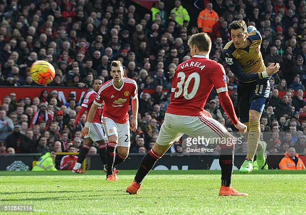 Mesut Ozil scores Arsenal's 2nd goal under pressure from Guillermo Varela of Man Utd during the Barclays Premier League match between Manchester...