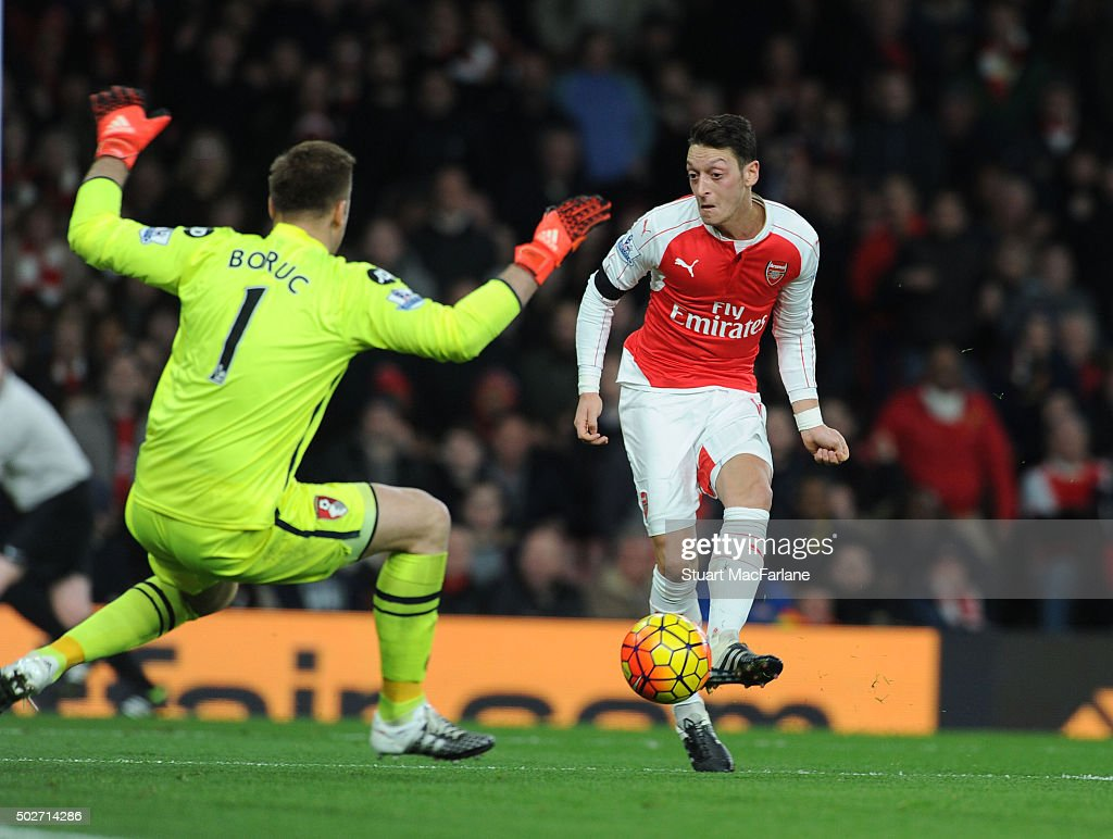 Mesut Ozil shoots past Bournemouth goalkeeper Artur Bouruc to score the 2nd Arsenal goal during the Barclays Premier League match between Arsenal and A.F.C. Bournemouth at Emirates Stadium on December 28, 2015 in London, England.