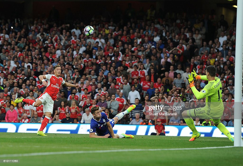 Mesut Ozil shoots past Chelsea goalkeeper Thibaut Courtois to score the 3rd Arsenal goal during the Premier League match between Arsenal and Chelsea at Emirates Stadium on September 24, 2016 in London, England.