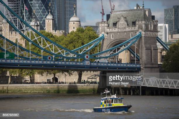 A met police launch boat in the waters of the River Thames beneath the Victorianera Tower Bridge with the Norman Tower of London in the capital's...