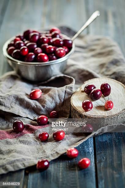 Metal bowl of cranberries, Vaccinium macrocarpon, on kitchen towel and wood