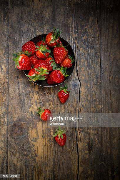 Metal bowl of strawberries on dark wood, view from above