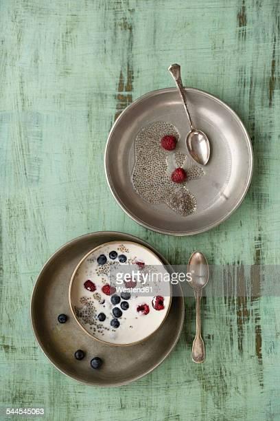 Metal bowl of vanilla yoghurt with chia, Salvia hispanica, blueberries and raspberries on green wood