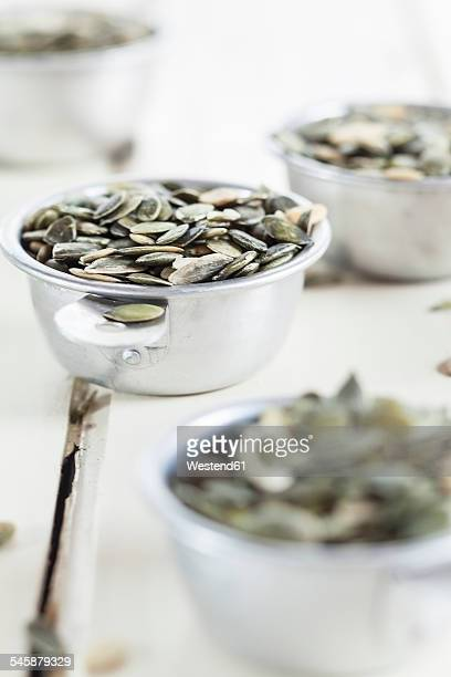 Metal bowls of pumpkin seeds on white wood