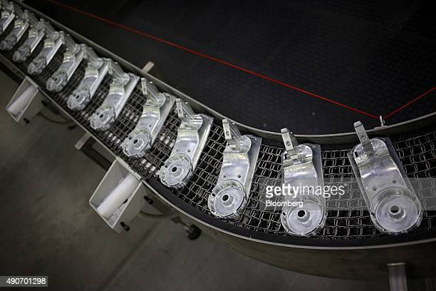 Metal components for stand mixers move down a conveyor belt on the production line at the Whirlpool Corp KitchenAid manufacturing facility in...