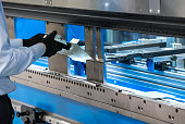Metal cutting and bending machine. Man cut metal sheet
