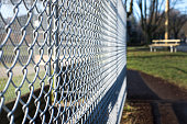 metal fence cage in a soccer field, park bench behind, sunny day, closeup, detail, horizontal