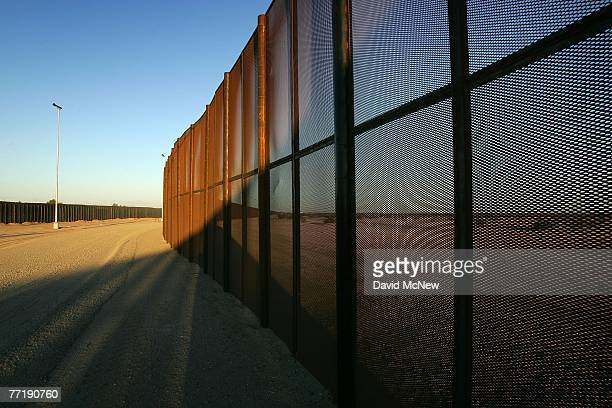 A metal fence recently constructed by National Guardsmen forms a doublefence border barrier in a dusty nomans land of denuded desert that runs along...