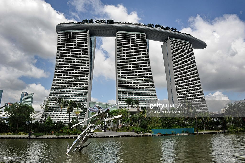 A metal figurine of a dragonfly sits in a lake against a backdrop of Marina Bay Sands hotel resort in Singapore on January 18, 2013. Singapore escaped a technical recession after the economy grew in the fourth quarter thanks to a boost from services, government data showed earlier this month, but prospects for 2013 remain gloomy.