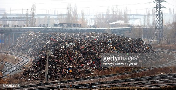 Metal Garbage By Railroad Tracks Against Sky