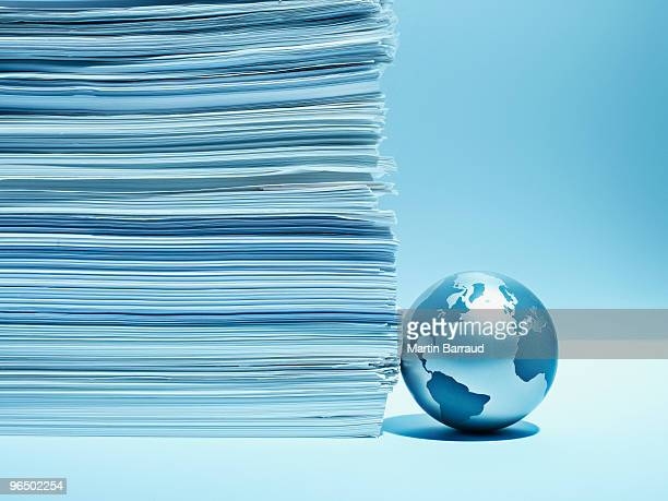 Metal globe against stack of paper