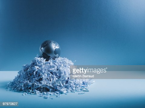 Metal globe on pile of shredded paper : Stock Photo