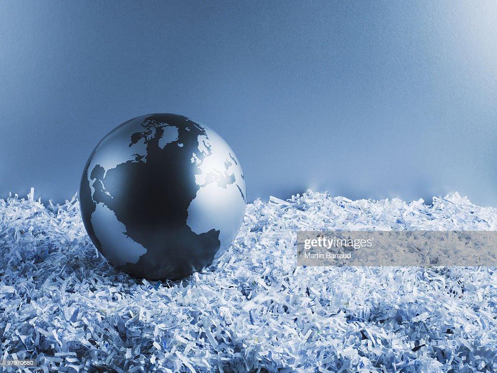 Metal globe on shredded paper : Stock Photo