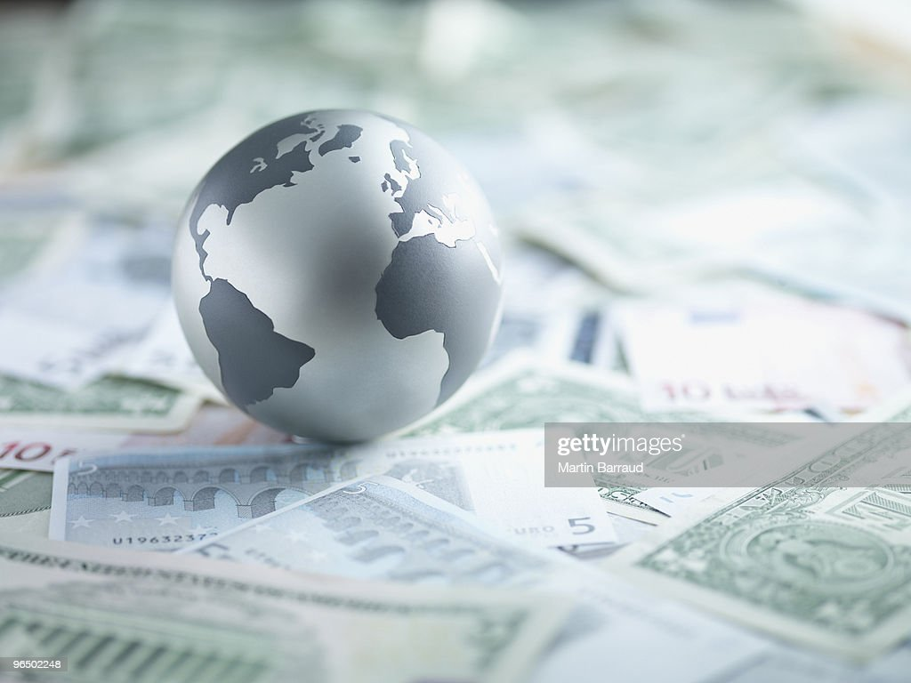 Metal globe resting on paper currency : Photo