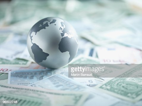 Metal globe resting on paper currency : Stock-Foto