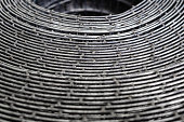 Metal mesh, twisted in rolls. Iron mesh for fence installation. Top view of the twisted lattice. Texture, background