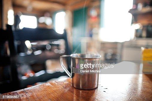 Metal mug on the table at a mountain house.